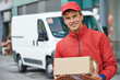 Leinwanddruck Bild - delivery man with package outdoors