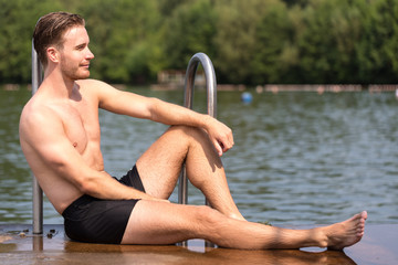 Man relaxing in the sun at public swimming pool