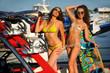 Two hot bikini models  posing on the sporty  speed-boat.