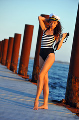 Sailor model holding binoculars and standing on the pier.