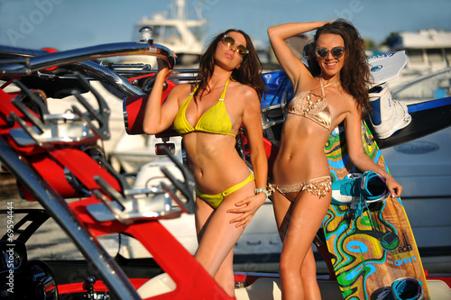 Two hot bikini models  posing on the sporty  speed-boat.