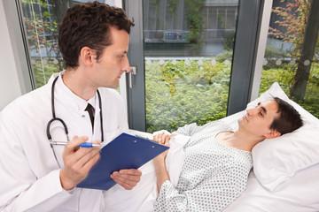 Arzt kommt zur Visite ans Krankenbett