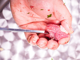 Closeup of a chef entering pieces of meat onto a skewer, making