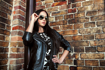 Beautiful woman in jacket and sunglasses posing over brick wall
