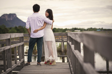 Beautiful married couple on the wooden bridge