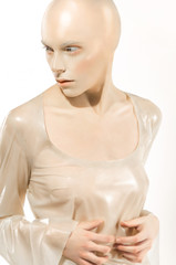 Conceptual fashion shot with bald girl in latex outfit