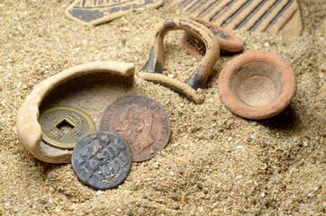 pezzi di vasi antichi su sabbia con monete antiche