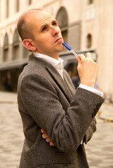 man thinking holding a pen