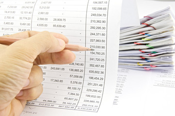 Man auditing account by pencil with pile of paperwork