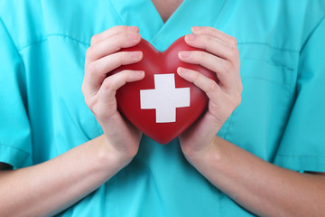 Red heart with cross sign in doctor hand, close-up, isolated