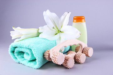 Wooden roller brush, towel, lily and shampoo on grey background