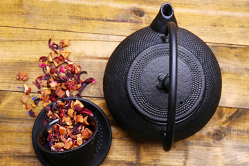 Black teapot, bowl and hibiscus tea on color wooden background