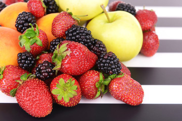 Ripe fruits and berries on striped background