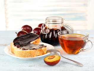 Bread with plum jam and tea on wooden table