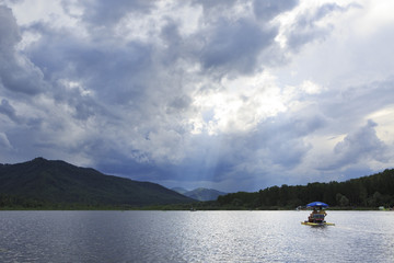 Sunrays breaking through storm clouds over mountain lake