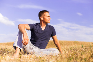 Young man relaxing on the sunny meadow.