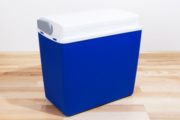 The dark blue plastic container on a floor