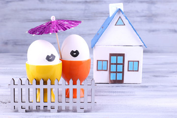 Eggs in egg cups near house and fence on grey wooden background