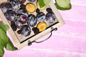 Ripe sweet plums on tray, on pink wooden table