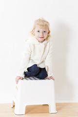 kneeling little girl wearing white sweater