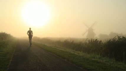 Young man running at foggy sunrise.