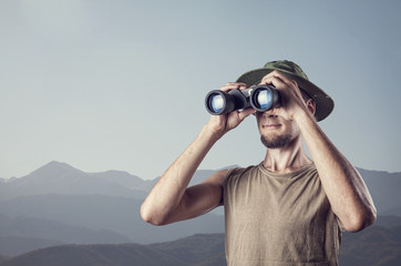 Man with binocular in the mountains