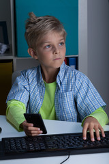 Young boy with phone and computer