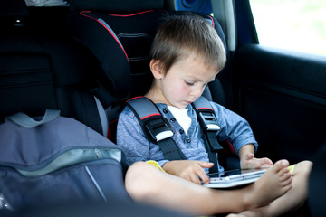 Cute boy, playing on tablet in the car