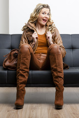 woman wearing brown clothes and boots with a handbag sitting on