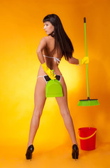 Girl in lingerie with broom on a yellow background.