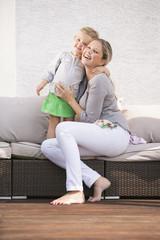 Mutter und Tochter umarmen einander auf Sofa