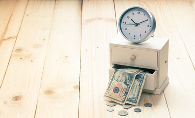 Clock and box of money on wooden background, vintage color effec