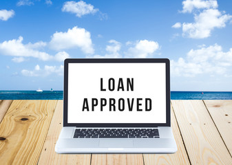 Loan application approved on Laptop computer screen with seascap