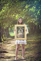 Girl with a paint of herself in the woods