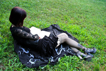 Sexy Witch reading spell book on the grass