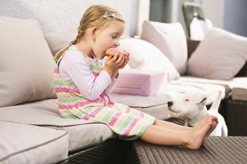 Junges Mädchen ißt Donut Hund wartet neben Sie.