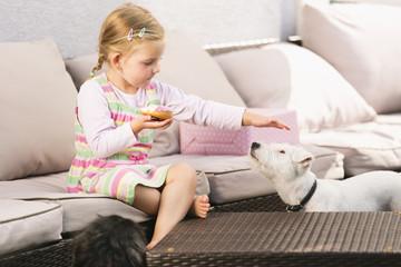 Junges Mädchen sitzt auf Sofa, ißt Donut, streichelt Hund