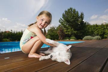Kleines Mädchen spielt mit Hund bei Swimming Pool