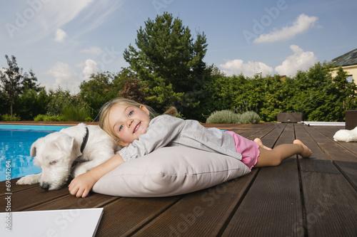 Kleines Mädchen spielt mit Hund bei Swimming Pool - 69614264
