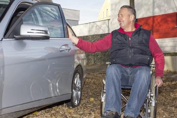 Man in a wheelchair in the fall next to their car
