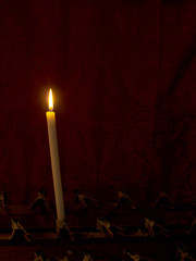 Prayer. Single church candle burns in front of red curtain.