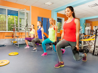 Four women in a row excursing inside fitness club