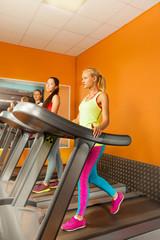 Three girls running in the gym on treadmill