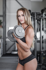 Blonde fitness model workout with dumbbell