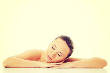 Beautiful nude woman is lying on her hands.