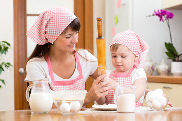 Mother and kid preparing cookies together at kitchen