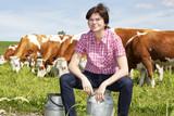 Farmer with milk churns at their cows