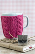 Blue cup in a pink sweater standing on an old notebook