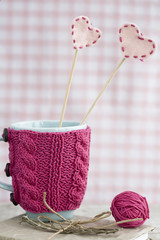 Blue cup in a pink sweater with felt hearts
