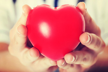 Red heart held by a female doctor.